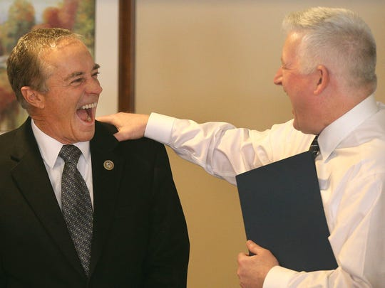 Rep. Chris Collins, left, shares a big laugh with Democratic Assemblyman Mickey Kearns while visiting a Buffalo care facility to help resident Dorothy Menke celebrate her 100th birthday.
