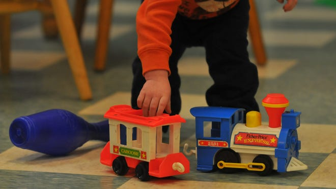 A child plays with a toy train while staying at the Genesis shelter.