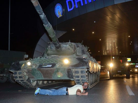 July 16, 2016 file photo a man lays in front of a tank in the entrance to Istanbul's Ataturk airport. Members of Turkey's armed forces said they had taken control of the country, but Turkish officials said the coup attempt had been repelled early Saturday morning in a night of violence that left several people dead, according to state-run media.