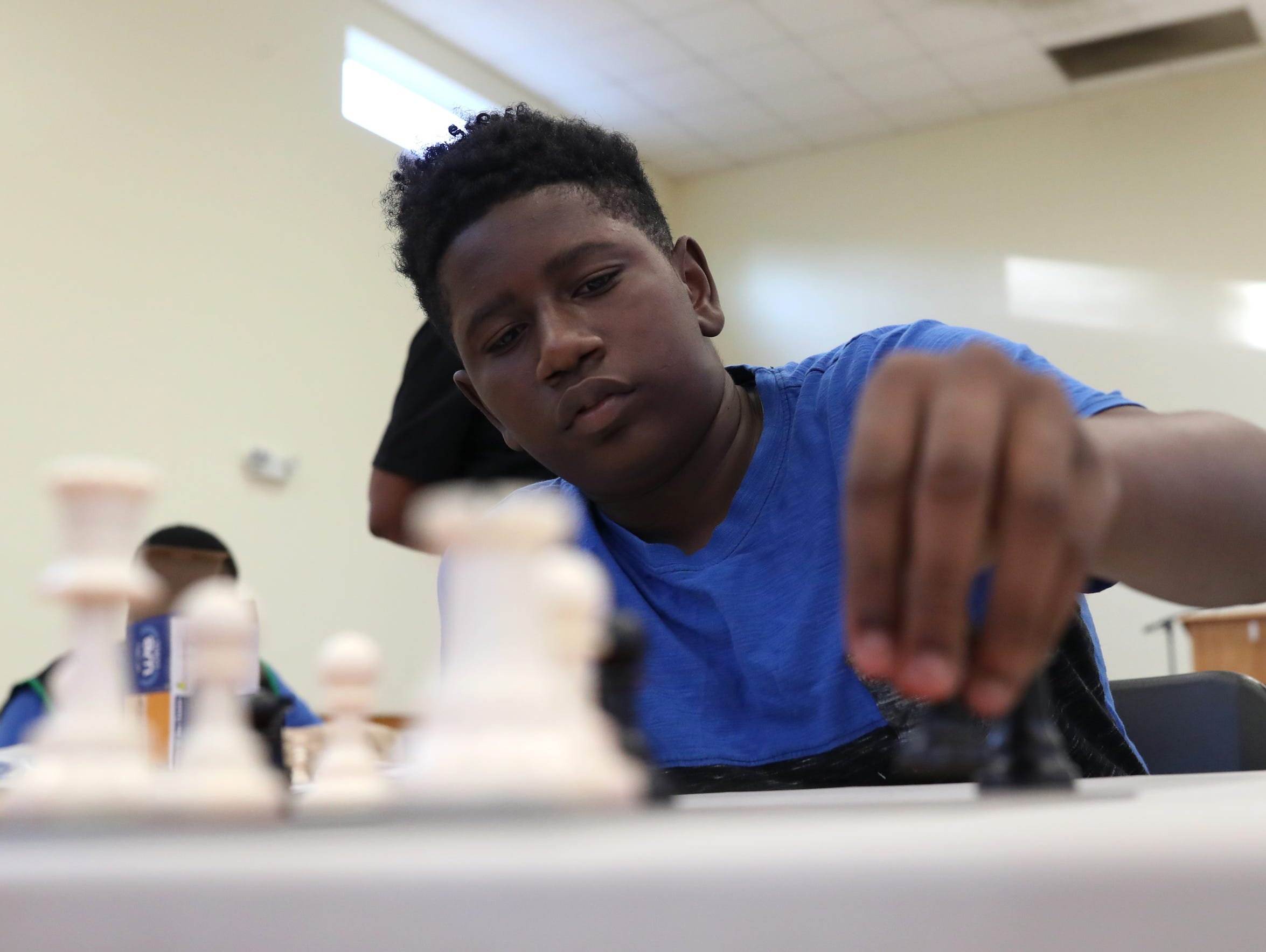 Jaylan Smith, 15, plays a game of chess with Alan Wilson,
