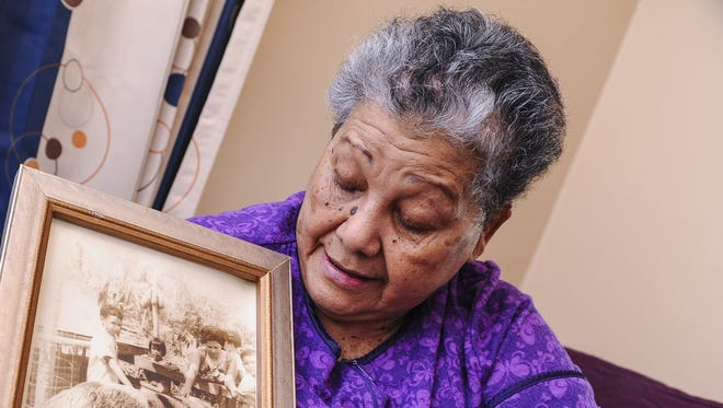 World War II survivor Bernedita Hamamoto looks over a photo, of her younger self when her family raised hogs, while at her home in Agana Heights on June 23. Rick Cruz/Pacific Daily News/rmcruz@guampdn.com