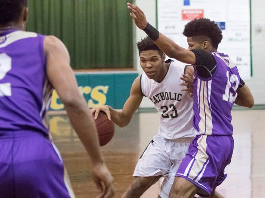 Nitrell Bledsoe (23) drives past Steph'on McMillan (13) during the Marianna vs Catholic Region 1-5A quarterfinal basketball game at Catholic High School on Thursday, February 22, 2018.