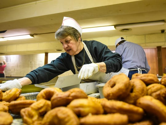 Joanne Arnold sugars fasnachts as volunteers at St. Cecilia's made fasnachts on Monday, February 8, 2016. The volunteers will have made fasnachts for three days straight and expect to sell 9,510 dozen.