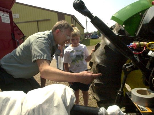Bill Hanson explains to 9-year-old Brandon, the dangers associated with the operation of a tractor during a farm safety event at the Lincoln County Fairgrounds.