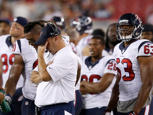 Houston Texans coach Bill O'Brien, front left, lowers his head as Terrance Lloyd (63) and Brandon Harris (26) stand near the coach late in the second half of an NFL preseason football game against the Arizona Cardinals on Saturday, Aug. 9, 2014, in Glendale, Ariz.  The Cardinals defeated the Texans 32-0. (AP Photo/Ross D. Franklin)