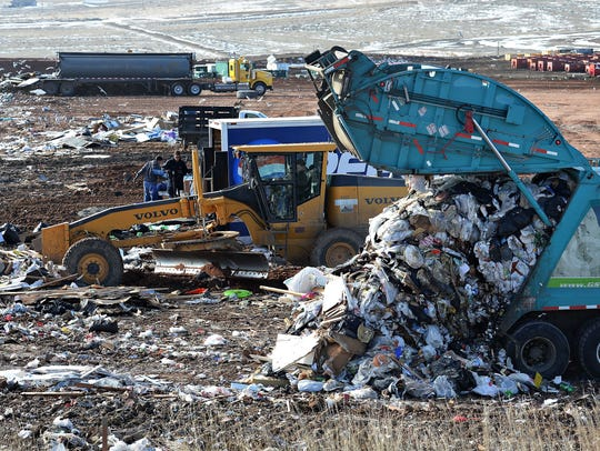 A trash truck empties its contents at the Larimer County