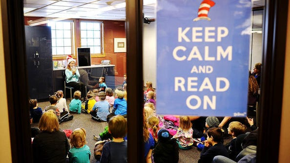 Library associate, Alicia Klein, reads to children during a Dr. Seuss-themed story time as a part of Read Across America Day honoring Dr. Seuss' birthday, which was March 2, on Thursday, March 6, 2014, at the Ronning Branch of the Siouxland Libraries in Sioux Falls.