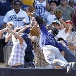 Colorado Rockies third baseman Nolan Arenado (28) leaps into the stands but cannot reach a foul ball hit by the San Diego Padres' Wil Myers during the sixth inning of a baseball game Monday in San Diego, Calif.