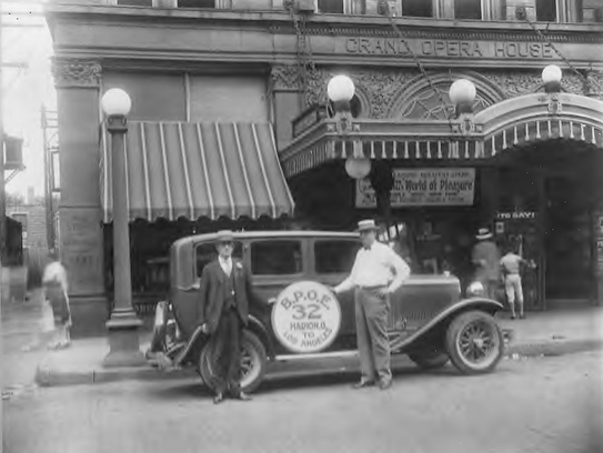 Two man stand outside of theater on State Street in
