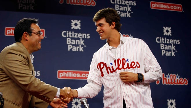 Philadelphia Phillies general manager Ruben Amaro Jr., left, shakes hands with newly-drafted pitcher Aaron Nola during a news conference before a baseball game against the San Diego Padres, Tuesday, June 10, 2014, in Philadelphia. (AP Photo/Matt Slocum)