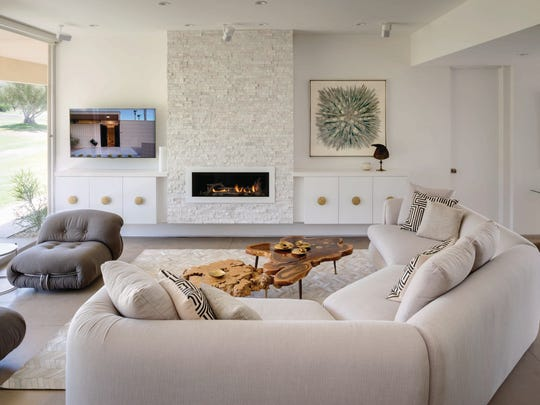 A simple, subdued color scheme, layered on a poured concrete floor, has a vintage Stephen Chase sofa as its inviting centerpiece. Split-face quartz sourced at Victory Tile & Marble gives the floating fireplace its sparkling, rock-candy look. A vintage 1960s painting plays nicely with the bronze horse from an Avignon, France, flea market that tops the floating credenza.