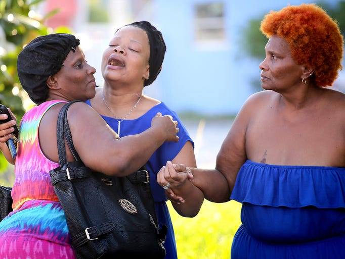Bennae Robinson, center, aunt of shooting victim Kevin Richardson, reacts to the death of her nephew after a shooting outside an apartment complex June 24 in Liberty City, Fla.  Two people were killed and up to eight others wounded in the early morning shooting. Three people have been arrested.