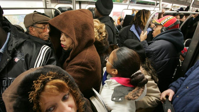 Passengers crowd into a subway car.