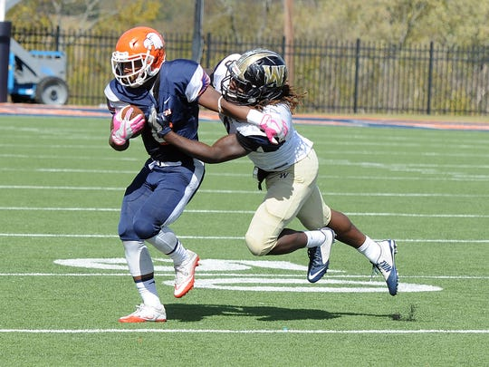 Carson-Newman running back Antonio Wimbush is dragged down from behind by Wingate's Ray Edwards Saturday at Burke-Tarr Stadium in Jefferson City.