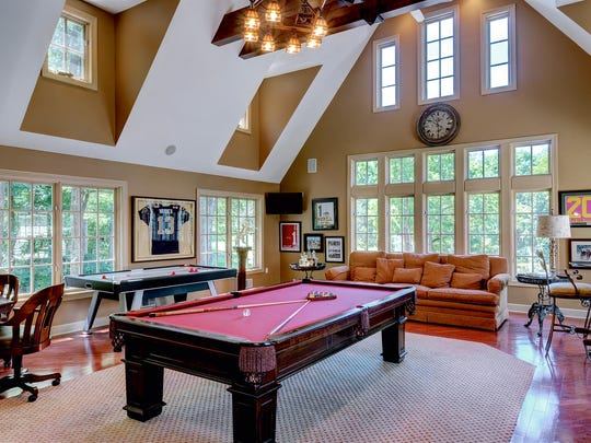 The game room has a beamed, cathedral ceiling, hardwood