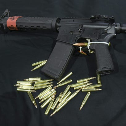 55.6 Nato bullets are shown with an AR-15 Rifle on