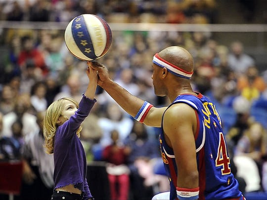 Kathleen Egan, 5, gets help from Flight Tim Lang as she learns to spin the ball on her finger after she was brought onto the court to play along with the Harlem Globetrotters as they entertained the crowds during a stop in Nashville.