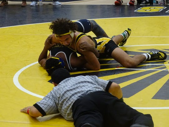 Watkins Memorial senior Dante Fair looks to the ref for a pin during a 170-pound match this past Saturday during the Division I sectional tournament.