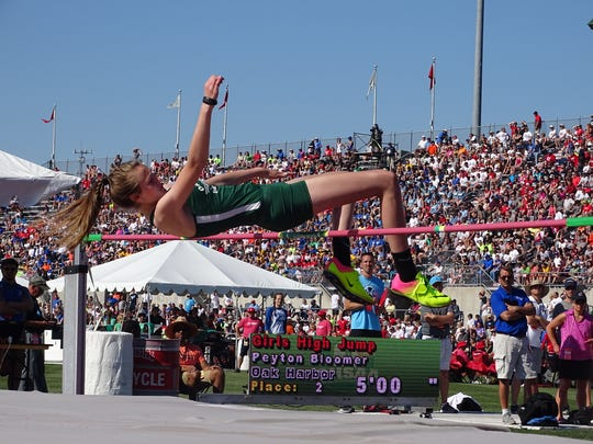 Oak Harbor's Peyton Bloomer  tries to clear the bar during the high jump at the Division II state track meet Friday at Jesse Owens Memorial Stadium.