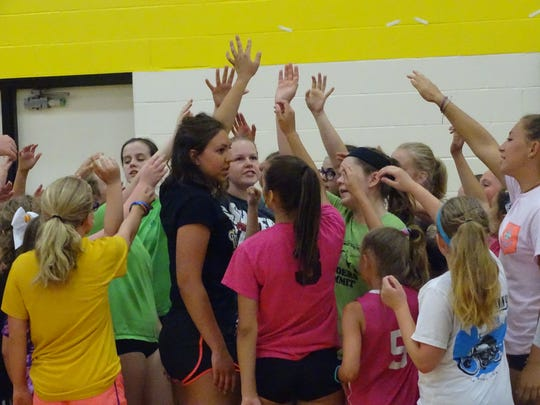 Watkins Memorial senior Kelsey Seas leads a huddle Monday during Watkins Memorial's youth volleyball camp.