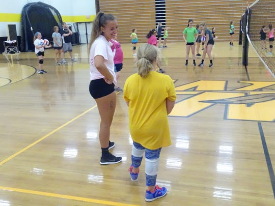 Watkins Memorial senior Margaret Musselman shares a laugh with sixth-grader Shelby Roush on Monday during Watkins Memorial's youth volleyball camp.
