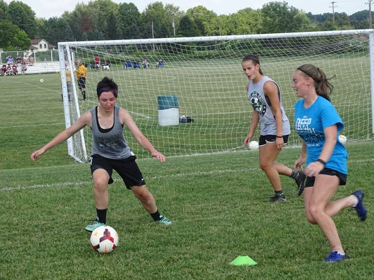 Licking Heights freshman Abby Hilderbrand, left, defends junior Kortni Starr, right, and sophomore Bella Whitney, back, in a 2-on-1 drill during a recent practice.