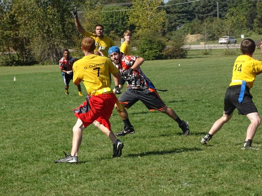 Jacob Gray, of Lunatics, pursues Primetime quarterback Dalton Clapper on Sunday during a Mid-State Flag Football League game at Evans Park in Hebron.