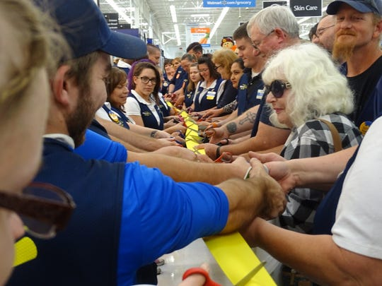 Walmart associates line up to cut a long ribbon, as