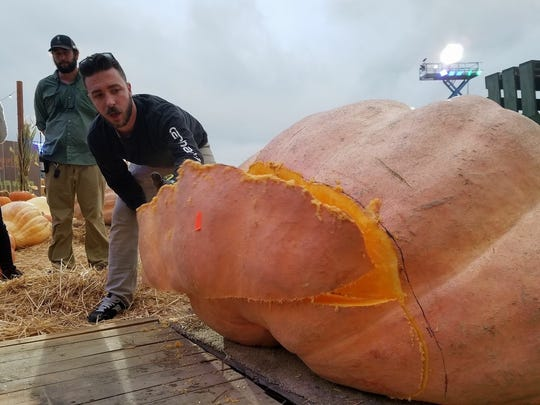 Pumpkin carver Adam Bierton works on a giant pumpkin.