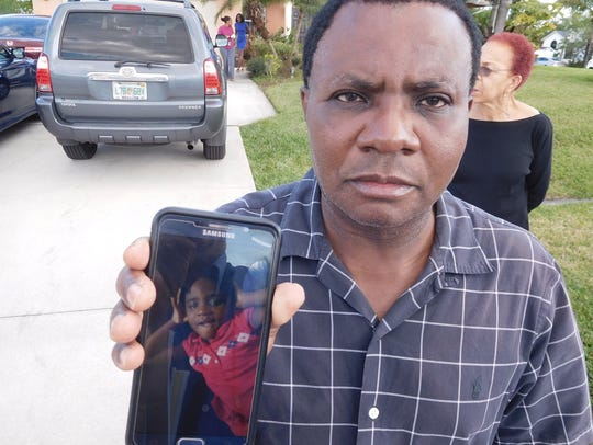 Remy Noel holds a cell phone with a photo of his daughter, Chelsea Noel, after she wandered away from her home.