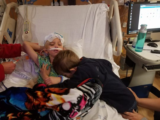 Elijah Daugherty leans on his brother Christian days before the scheduled surgery to remove his tumor.
