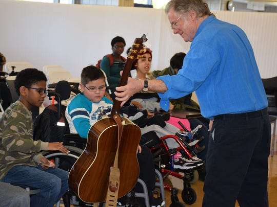 """John Sebastian, member of the Rock & Roll and Songwriters Halls of Fame, shows off his guitar to children at Blythedale Children's Hospital's on-site school, Mt. Pleasant-Blythedale U.F.S.D, where he answered questions ranging from his 1969 Woodstock appearance to penning the No. 1 hit in 1976, """"Welcome Back"""" (title song to the classic T.V. show """"Welcome Back, Kotter"""")."""