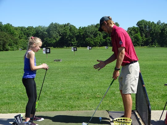 Granville Golfland instructor Nathan Nicholson discusses stance with Haylee McDonald, 10, of Newark, during a youth clinic Thursday.