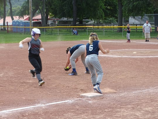 Newark Gray's Olivia Mutchler reaches third base as Granville's Mickey's Roofing's Maggie Gibson fields the ball and Claire Edwards covers on Monday during the Central Ohio Girls FastPitch 12U championship game in Saint Louisville. Newark won 7-4.