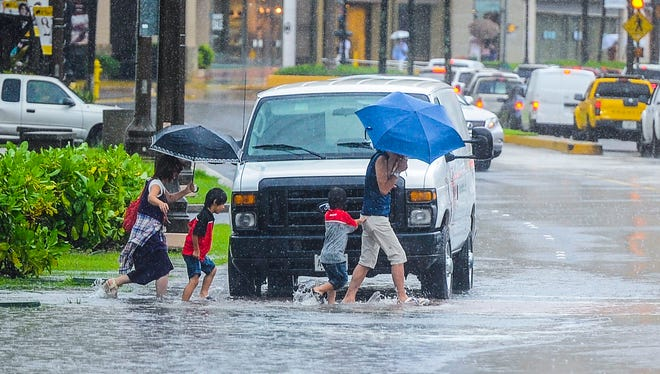 A family crosses San Vitores Road near the SandCastle in Tumon in this file photo. Fixes to Tumon flooding have been essentially halted due to the requirement to monitor the habitat ofan endangered bird, the Marianas moorhen.
