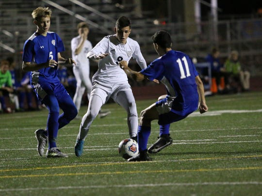 Naples' Luis Baldivieso, center, tries to maintain possession during the Golden Eagles' match with Barron Collier at Staver Field on Thursday. With a 3-0 win over Barron Collier, the Eagles secured the top seed in the district with an undefeated record of 6-0-2.