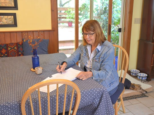 Elizabeth Juckett grades her students' English papers in the quiet of her house.