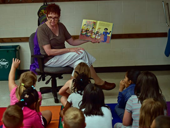 Teacher Barb Burhman reads to kids this morning during