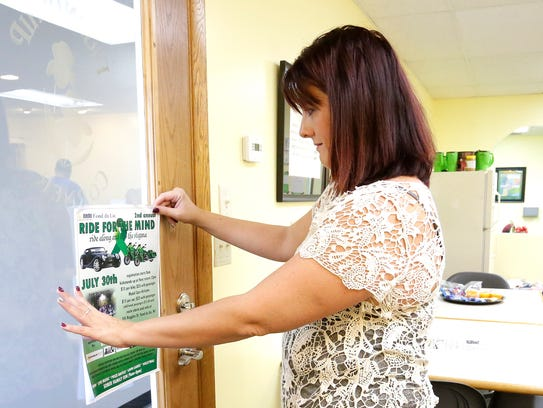 Brenda Neuman hangs a Ride for the Mind poster at Friendship