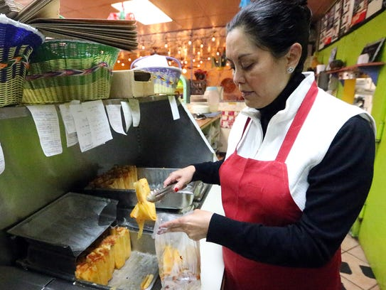 Manager Carla Monsisvais fills a bag with freshly made