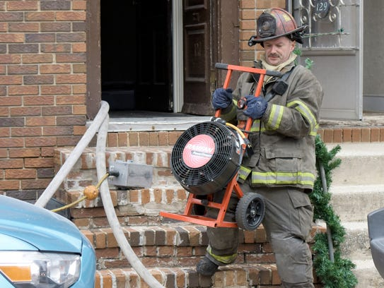 A firefighter removes a fan that was used to clear