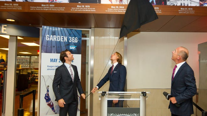 Rangers players Dominic Moore, left, and Carl Hagelin unveil a photo of the Rangers celebrating their Eastern Conference title last May. The photo, the latest addition to an exhibit of historical images at the Garden, was unveiled Monday.