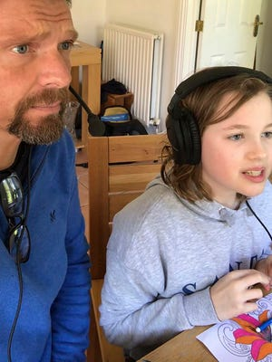 Cricket announcer Mark Church takes a selfie photo with his daughter Isabelle, in Cardiff, Wales, Sunday March 22, 2020, while they record one of the video commentaries.  Church has taken to doing short commentaries of some of the sport's major moments alongside his 10-year old daughter at their home or in the car, filling the void in his working life caused by the coronavirus outbreak.  The highly contagious COVID-19 coronavirus can cause mild symptoms, but for some it can cause severe illness including pneumonia.