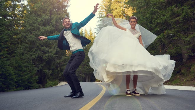 Bride and groom jumping, running and feeling great together.arms raised.photo taken on the road.