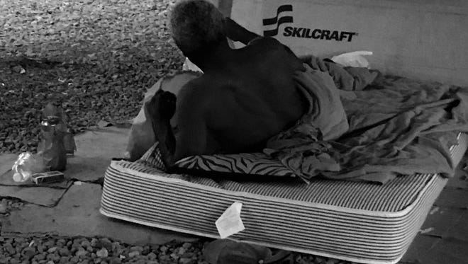 A homeless man rests under the I-49 overpass.