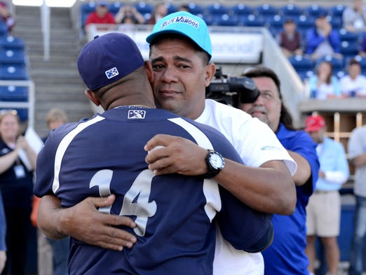 Pensacola Blue Wahoos catcher Rossmel Perez gets a hug from his father Santiago on Thursday as part of a surprise visit to watch his son play professional baseball. Santiago threw out the first pitch of the game against the Jacksonville Suns.