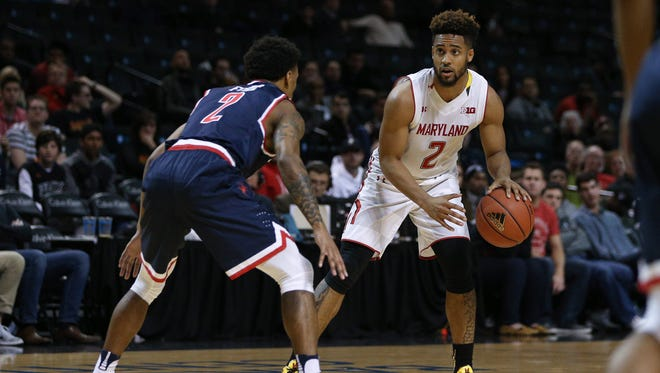 Maryland guard Melo Trimble (2) looks to pass while defended by Richmond guard Khwan Fore (2) during the first half.