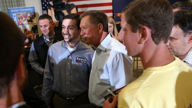 John Kasich, Ohio governor and the 16th major candidate seeking the GOP's 2016 nomination, takes photos with crowd members during the Nashua Town Hall Meeting on Tuesday evening while officially campaigning in New Hampshire.