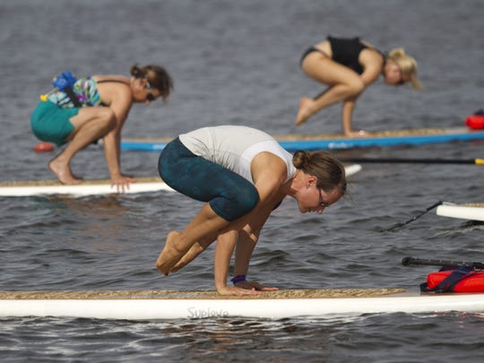 Anna Noble, center, practices the crow pose along with Mary Burnham, left, and Haley Bechet, right, off the Sanibel Causeway.