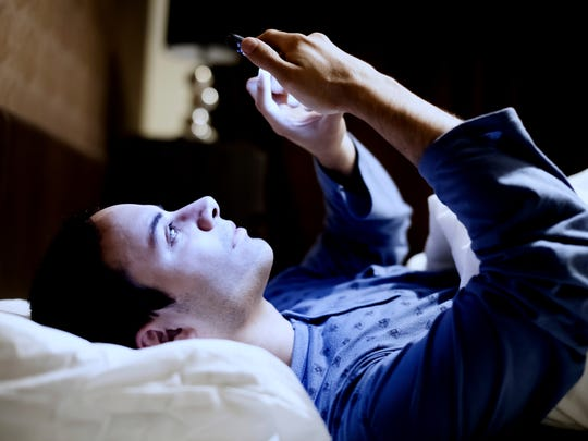 Man using his phone in bed.